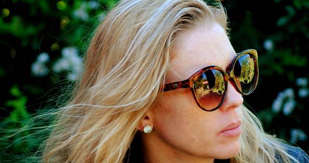 Woman wearing sunglasses, unhappy