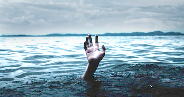 Hand reaching for help, drowning in ocean
