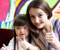 Teen with girl with down syndrome, thumbs up