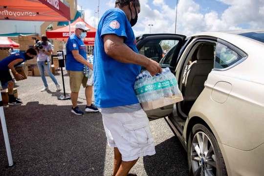 COH Volunteer loads bottled water into car