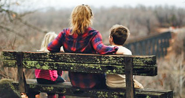 Mom, 2 kids, backs to us, sit on bench in nature