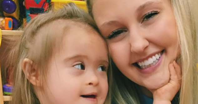 Toddler with down syndrome touches face of smiling woman