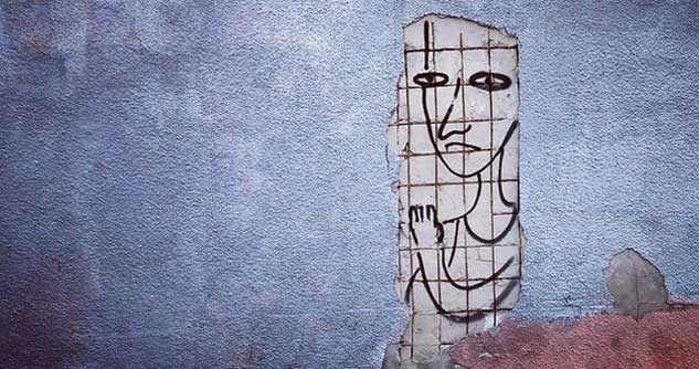 Mural on broken wall shows unhappy person behind bars